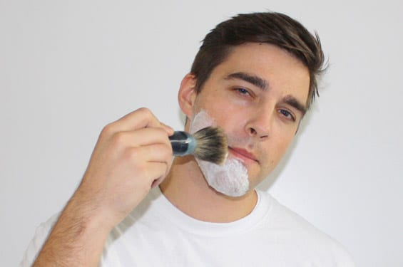 Young Man Using Shaving Cream Brush